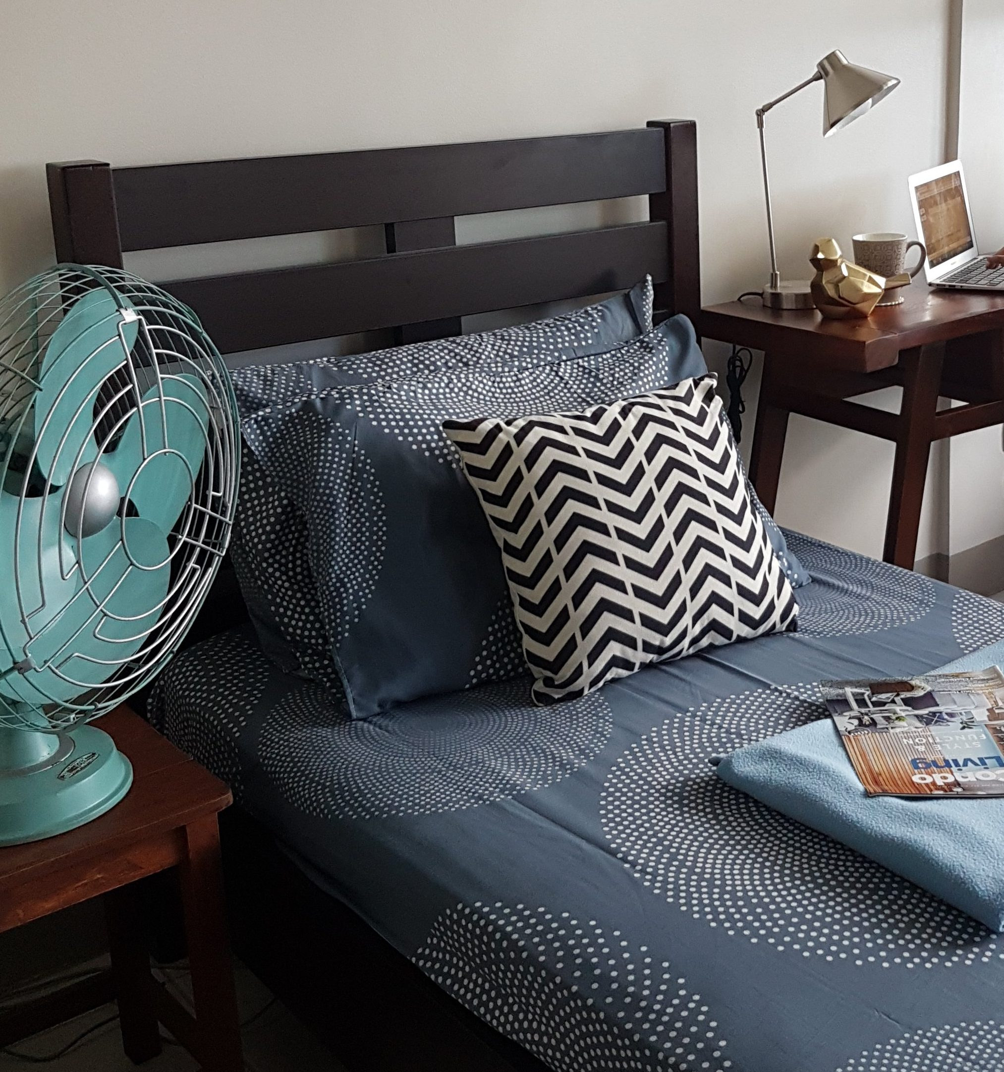 chevron print pillow on blue bed with vintage aqua electric fan