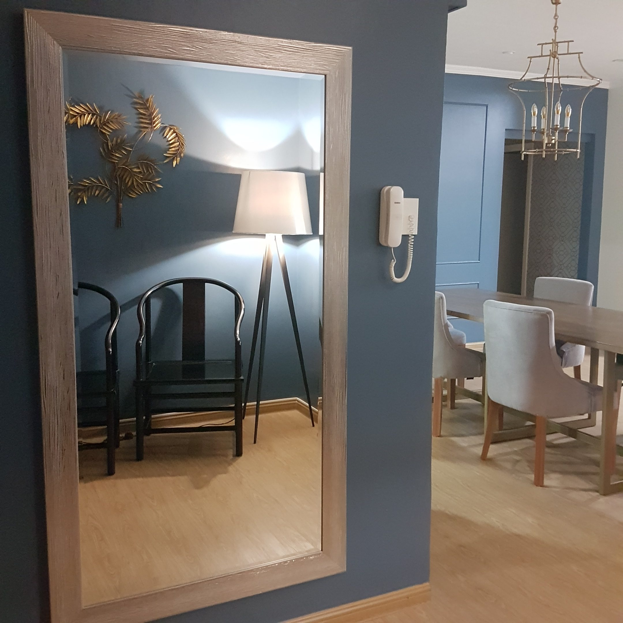 Full length mirror showing Chinese armchairs and a peek into the formal dining area