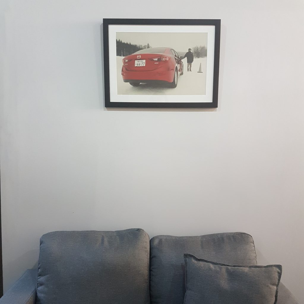 gray sofa under framed photo of red car