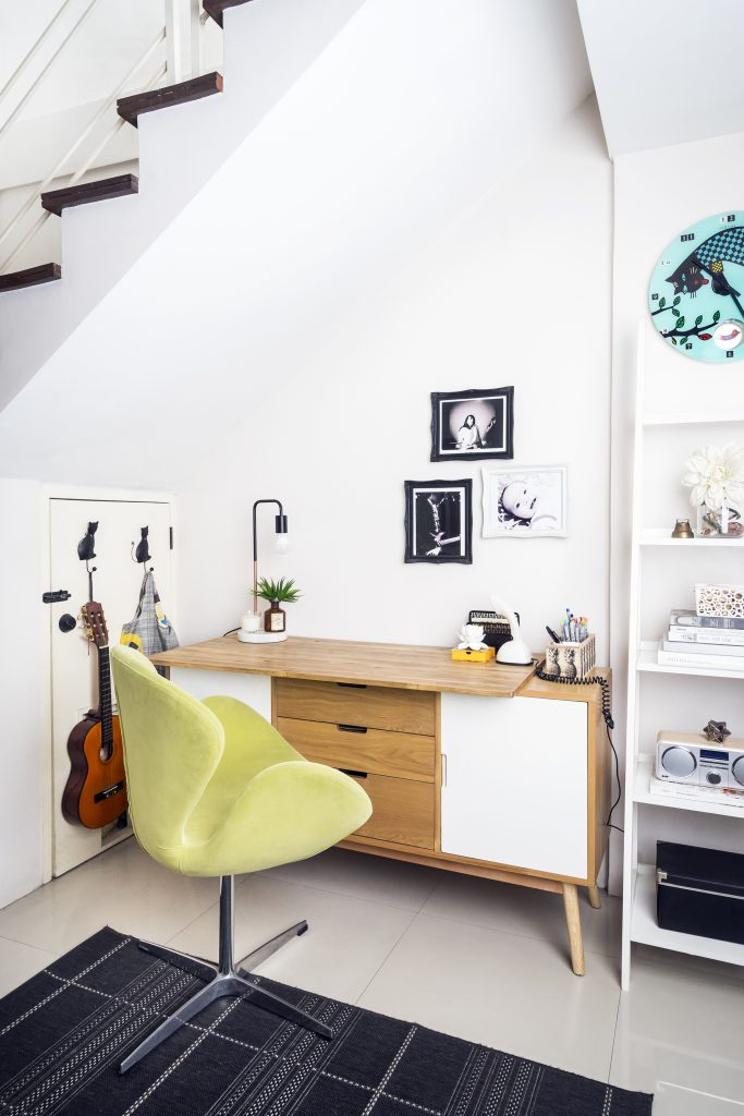 office nook under stairs with green chair