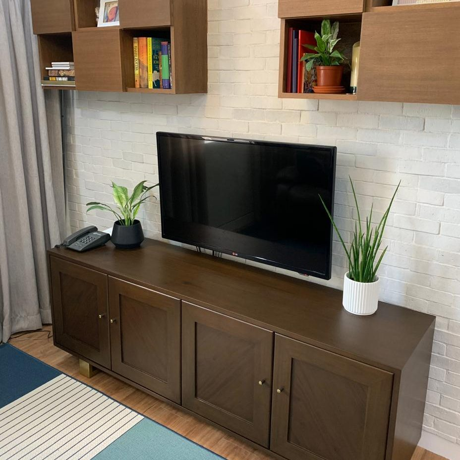 Wooden media cabinet and upper shelves against white brick wall