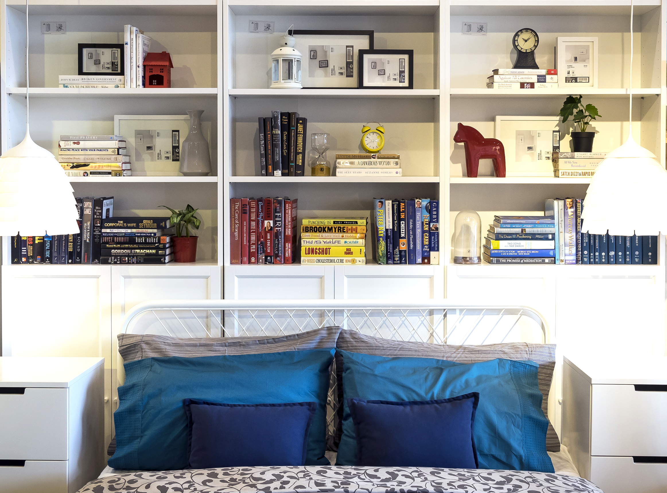 Well decorated Billy bookshelves behind Ikea bed with blue pillows