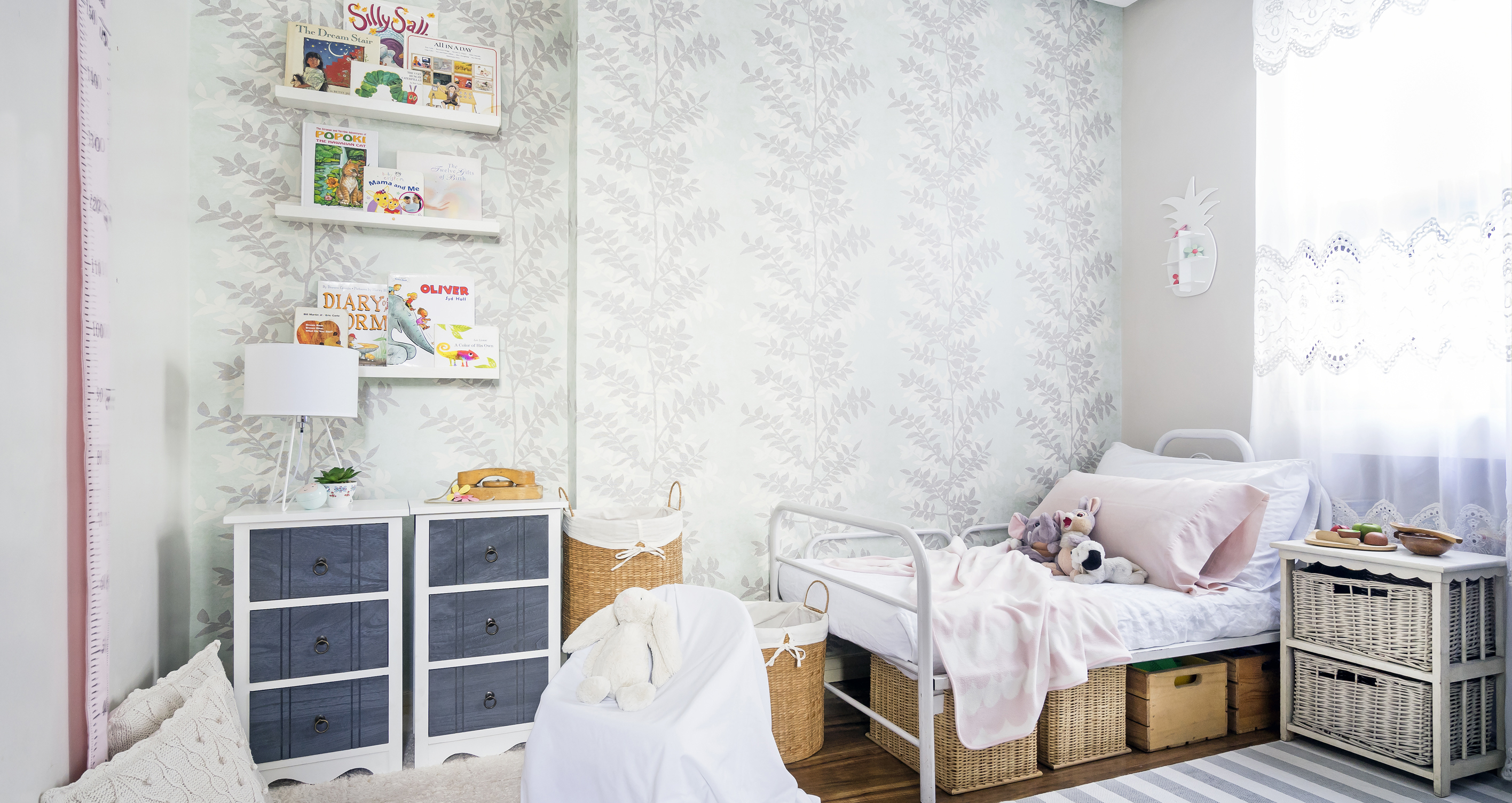 Nursery room with botanical-print wallpaper and pink and gray accents by interior designer Gal at Home