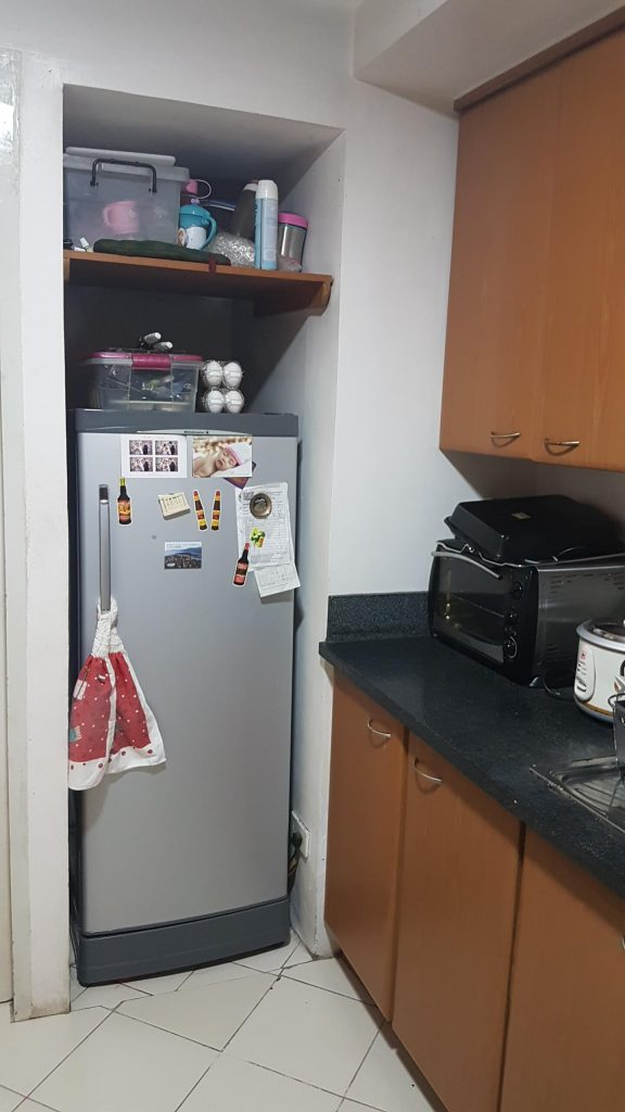small refrigerator and messy condo kitchen items