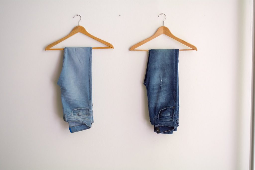 two pairs of jeans on clothes hangers, hung on wall