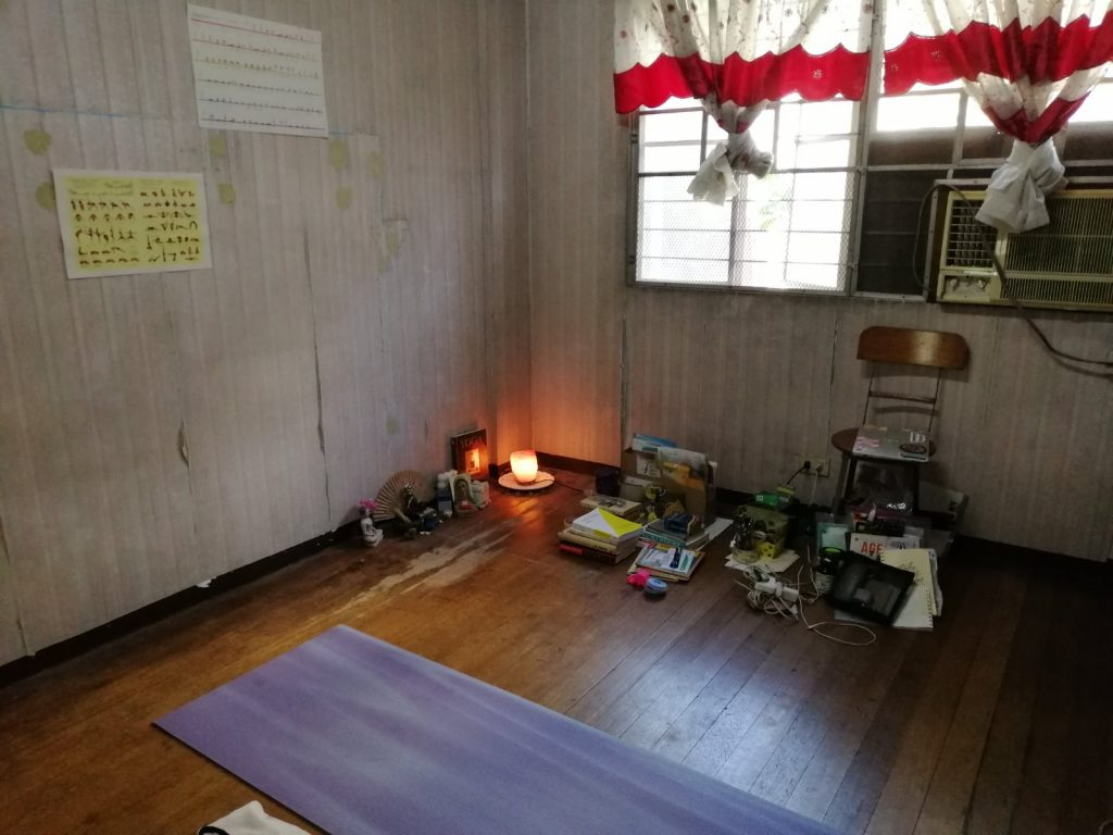 old bedroom with yoga mat and minimal furniture
