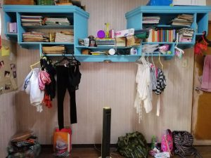 blue cluttered shelves with clothes on hangers