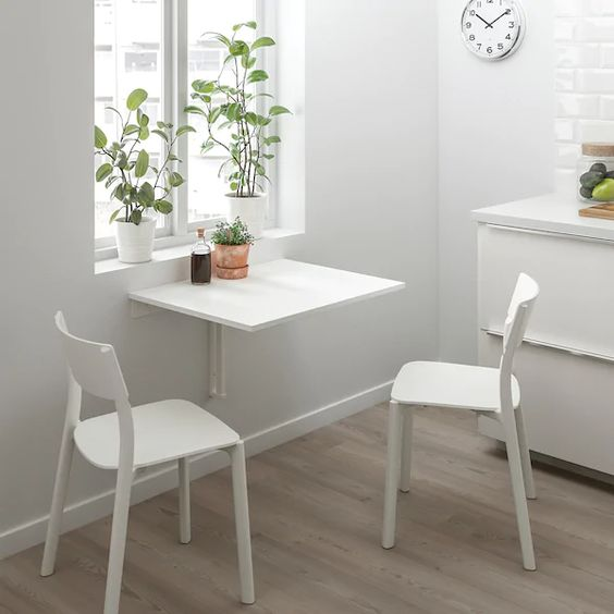 wall-mounted white dropleaf table with chairs