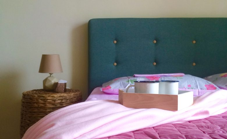 teal bed with pink sheets and a pink throw blanket
