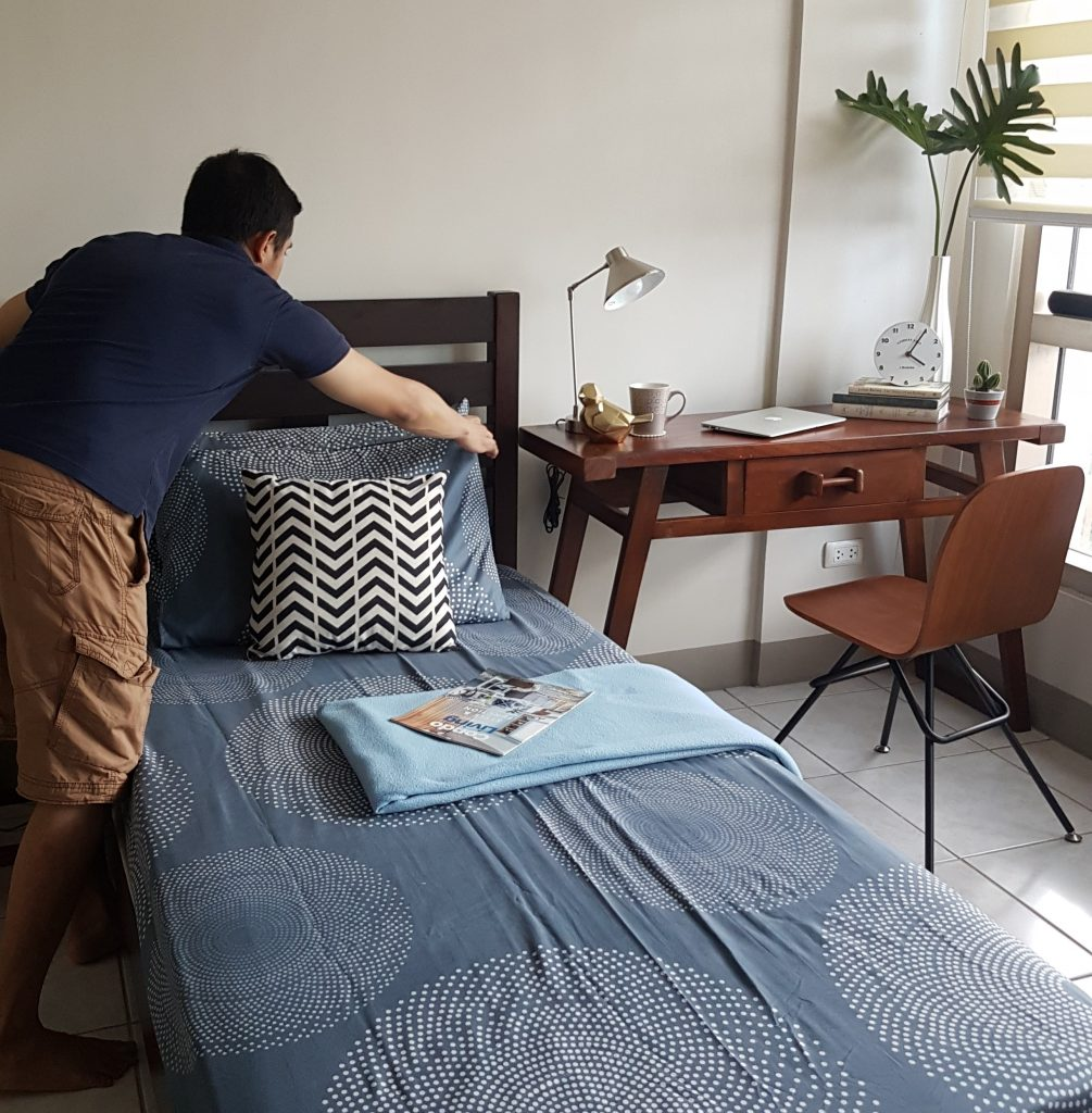 Man fixing pillows on bed