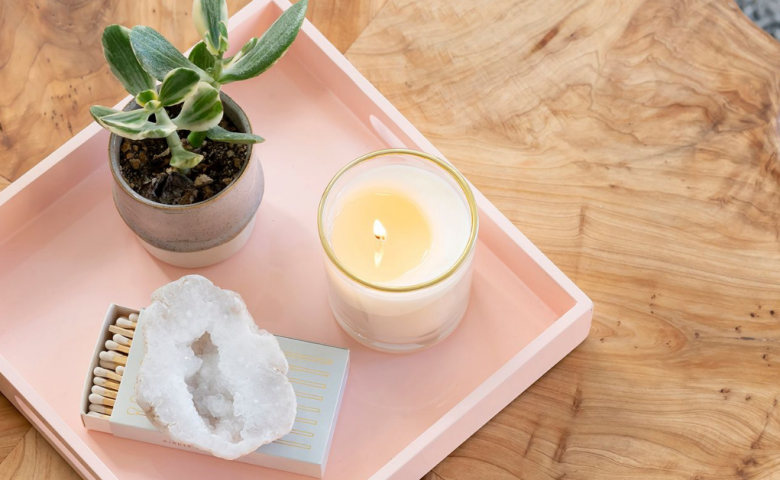 pink tray with candle, matchbox, and potted plant