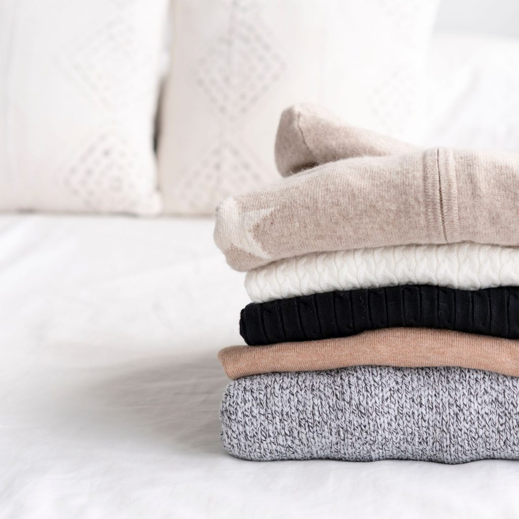 Stack of folded clothes on bed
