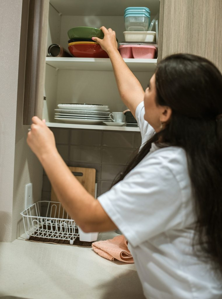 woman putting back bowls in cabinet